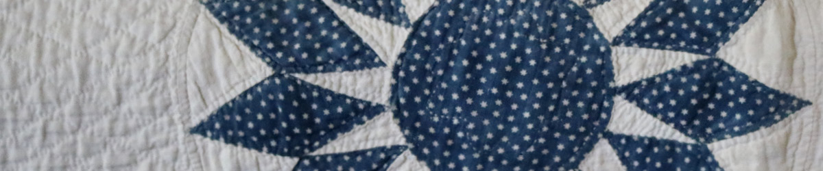 A quilt with a blue and white sun pattern on it.