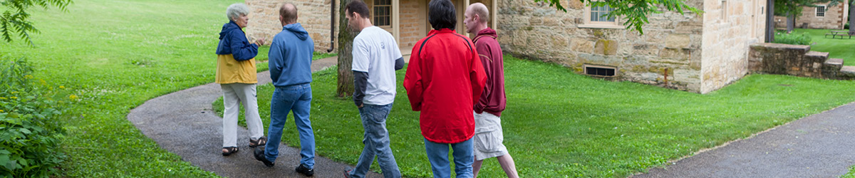 Visitors follow a guide along a path at the Sibley Historic Site.