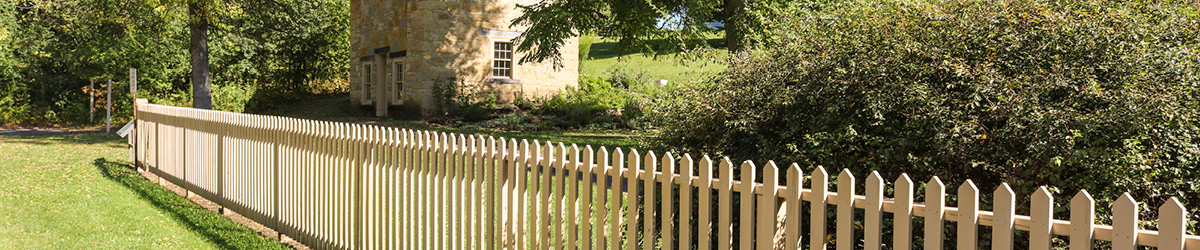 A picket fence borders the front of a stone house at the Sibley Historic Site.