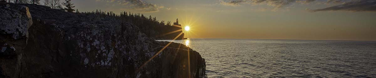 Split Rock in the distance, with the sun setting over Lake Superior.