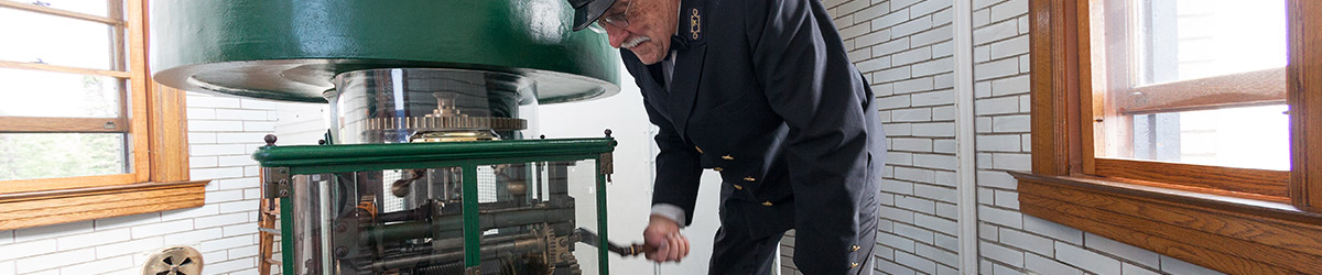 A lighthouse keeper turning a crank to rotate the lens