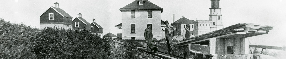 Men working on rail tracks with the lighthouse and several buildings in the background