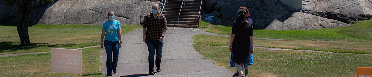 Four people wearing face masks walk near Split Rock Lighthouse.