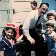Fun-loving Dick and Angie Krismer raised four children, including twins, in tight quarters at 472 Hopkins Street from 1956-1967. Here Dick Krismer braces for his birthday spanking! Dick Krismer and (l-r) Margaret Mary; Dick, Jr.; Rose Marie and Mary Theresa; in front of 470/472 Hopkins St., mid-1960s