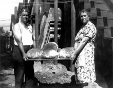 In the middle decades of the 20th century, Railroad Island felt like Little Italy. Filomena D'Aloia and Luciano Cocchiarella with homemade bread from an earthen oven, Hopkins Street, St. Paul, 1940