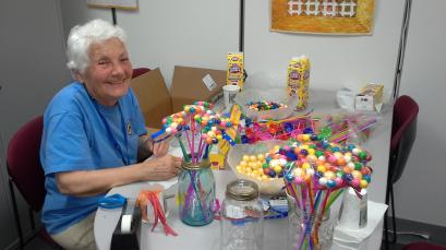 Volunteer making flowers from gumballs