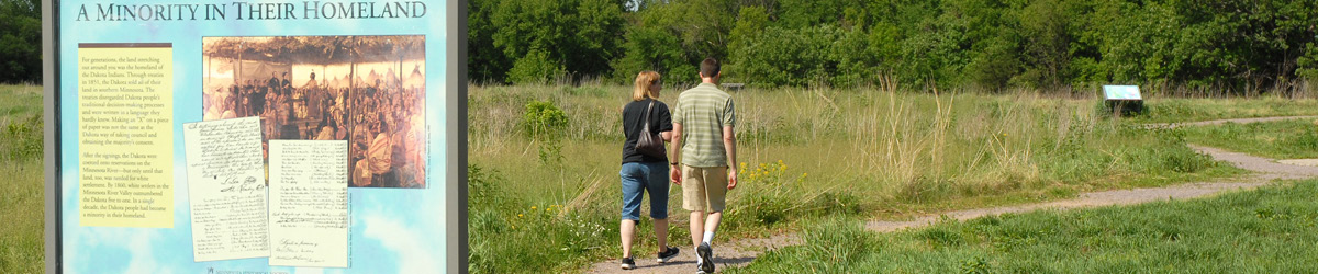 Two visitors walk outside on a dirt trail past an interpretive sign.