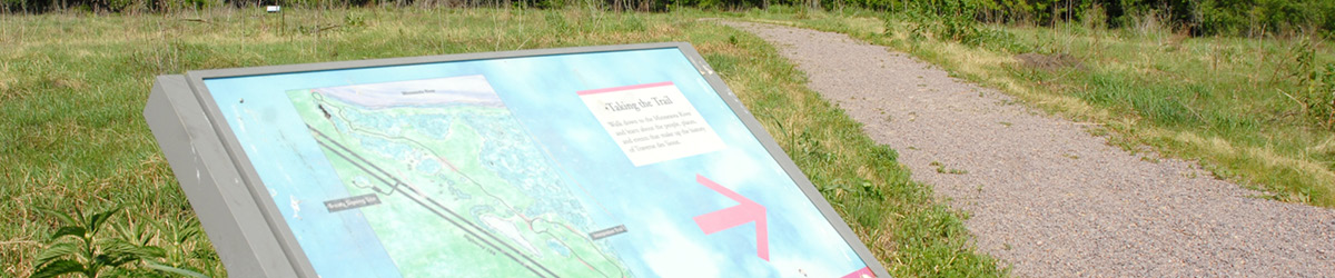 On the left side of a path, a sign with a map and a red arrow pointing to the right.