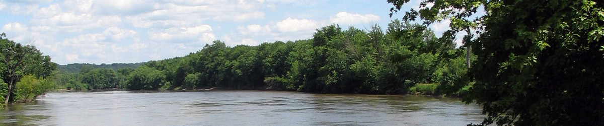 A curvy river surrounded by trees on both sides.