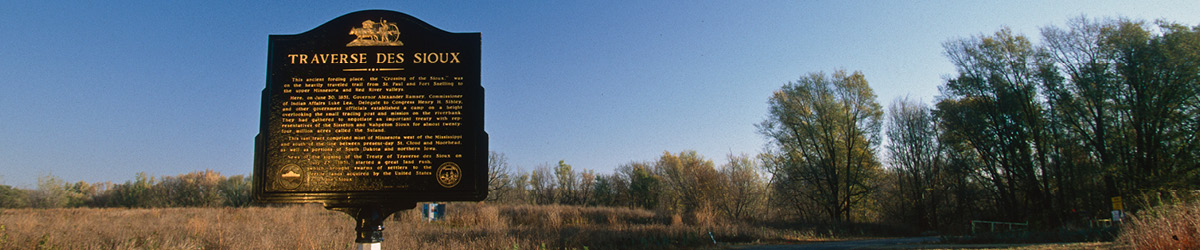 """A black sign with golden text on it, titled """"Traverse des Sioux""""."""